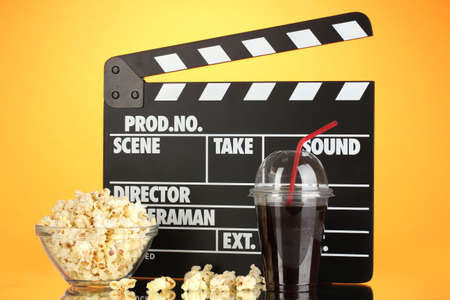 Movie clapperboard, cola and popcorn on orange background Stock Photo - 17209446