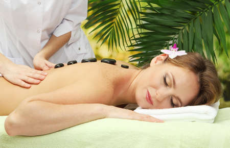 beautiful woman in spa salon  getting massage with stones, on palm leaves background Stock Photo - 17282327
