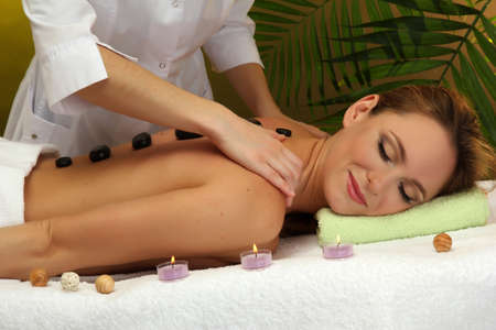 beautiful young woman in spa salon getting massage with spa stones, on green background Stock Photo - 17282489