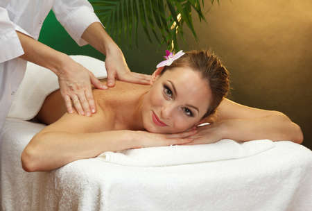 beautiful young woman in spa salon getting massage, on green background Stock Photo - 17282326