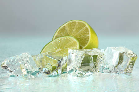 Ice cubes with lime on light blue background photo