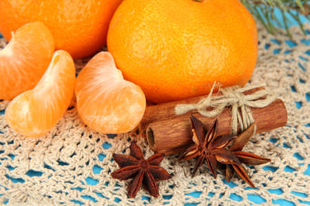 Tasty mandarines on napkin on blue background photo