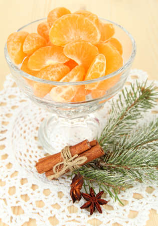Tasty mandarines slices in glass bowl on light background photo