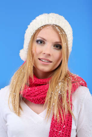 Young beautiful woman with snow on blue background photo
