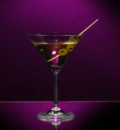 Martini glass and olives on dark background photo
