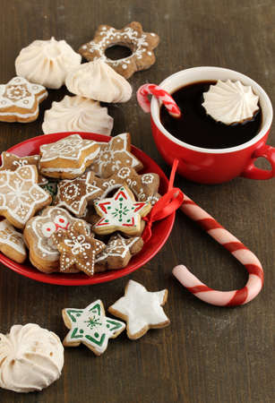 sugar cookie: Christmas treats on plate and cup of coffe on wooden table close-up