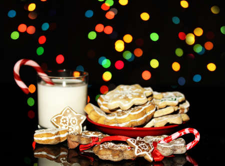Christmas treats with glass of milk on Christmas lights background photo