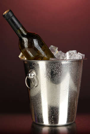 Bottle of wine in ice bucket on darck red background photo