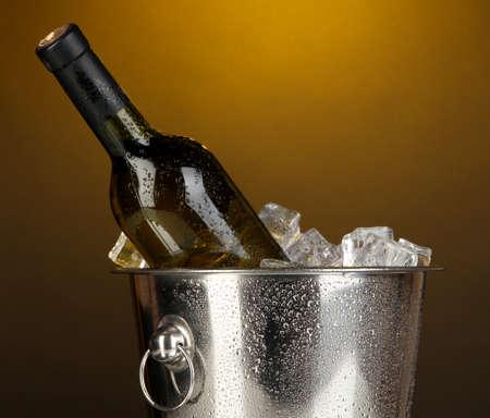 Bottle of wine in ice bucket on darck yellow background Stock Photo - 17216335