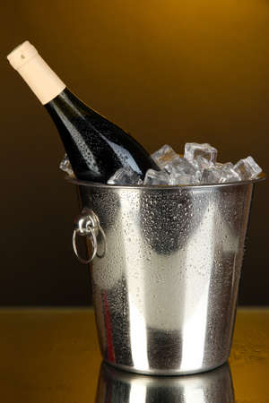 Bottle of wine in ice bucket on darck yellow background photo