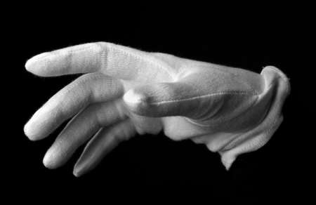 Hand in white glove making sign isolated on black Stock Photo - 17256013