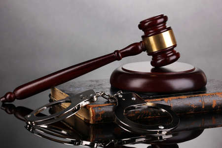 Gavel, handcuffs and book on law on grey background photo