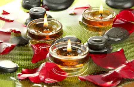 spa stones with rose petals and candles in water on plate Stock Photo - 17256022