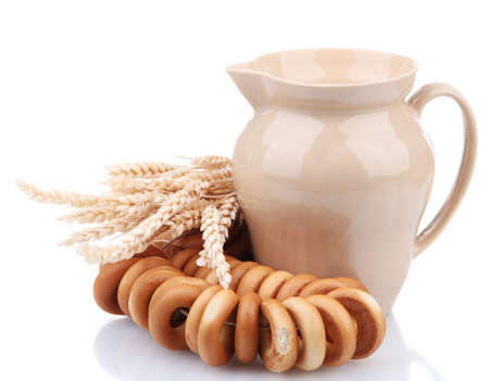 jar of milk, tasty bagels and spikelets, isolated on white photo