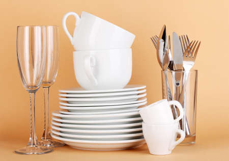 Clean white dishes on beige background Stock Photo