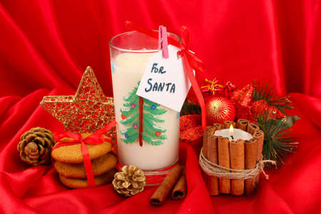 Cookies for Santa: Conceptual image of ginger cookies, milk and christmas decoration on red background photo