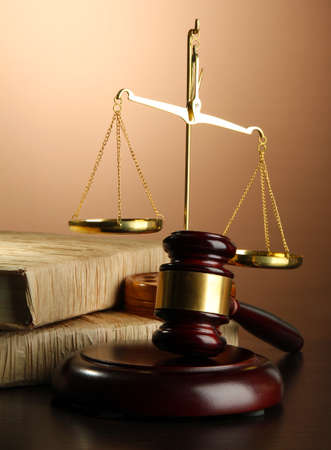 law business: Golden scales of justice, gavel and books on brown background Stock Photo