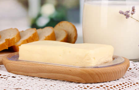 Butter on wooden holder surrounded by bread and milk on window background close-up Stock Photo - 17263834