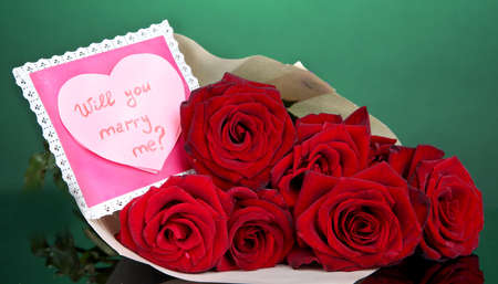 Beautiful bouquet of red roses with valentine on green background photo