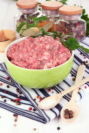 Bowl of raw ground meat with spices on wooden table Stock Photo - 17264134