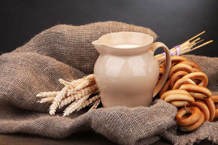 jar of milk, tasty bagels and spikelets on wooden table, on grey background photo