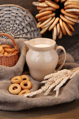 jar of milk, tasty bagels and spikelets on wooden background photo