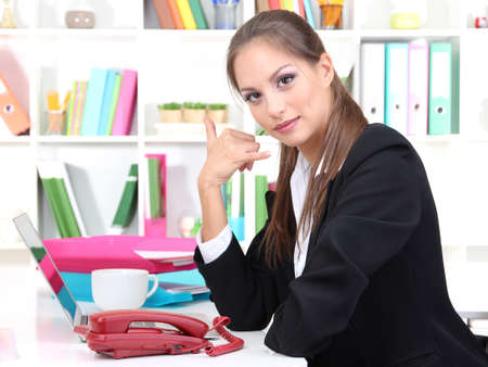 Young pretty business woman with phone and notebook working at office. Contact us photo