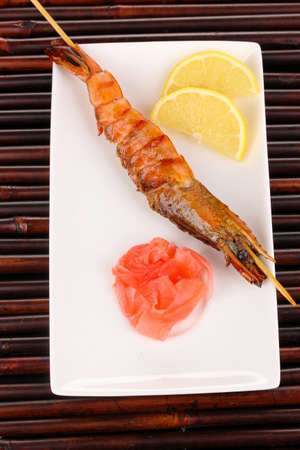 king prawn skewers on plate with ginger and lemon photo