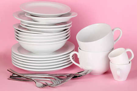 Clean white dishes on pink background photo