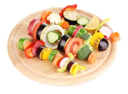 Sliced vegetables on wooden picks isolated on white photo
