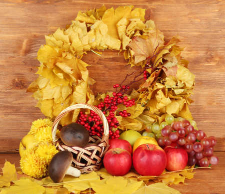Autumnal composition with yellow leaves, apples and mushrooms on wooden background Stock Photo - 17264133