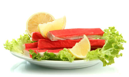 Crab sticks with lettuce leaves and lemon on plate isolated on white Stock Photo - 17263317