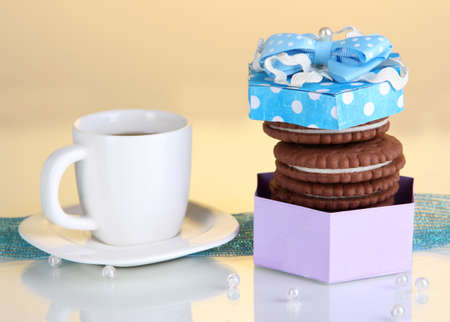 Chocolate cookies with creamy layer and cup of coffe on yellow background Stock Photo - 17263545