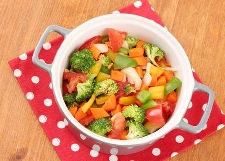 Vegetable stew in gray pot on color napkin on wooden background Stock Photo - 17264139