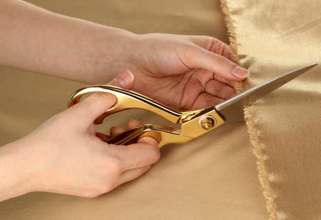 Seamstress cut gold fabric close-up photo