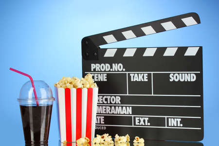 Movie clapperboard, cola and popcorn on blue background Stock Photo - 17263920
