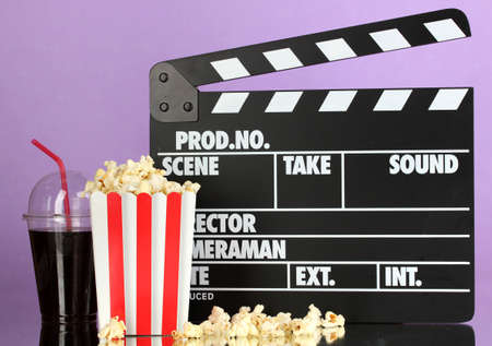 Movie clapperboard, cola and popcorn on purple background photo