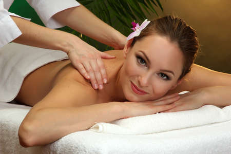 beautiful young woman in spa salon getting massage, on green background Stock Photo - 17761782