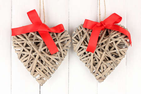 Wicker hearts with red bow on wooden background Stock Photo - 17263996
