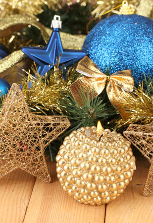 Christmas composition  with candles and decorations in  blue and gold colors on wooden background photo