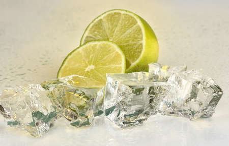 Ice cubes with lime on light yellow background photo