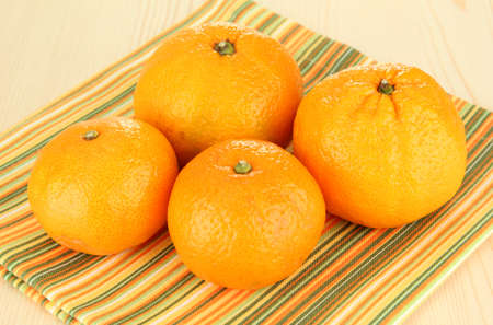 Tasty mandarines on napkin on light background photo