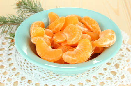 Tasty mandarines slices on color plate on light background photo