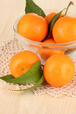 Sweet tangerines with leaves, on wooden background photo
