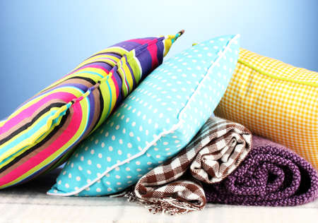 Plaids and color pillows on blue background photo