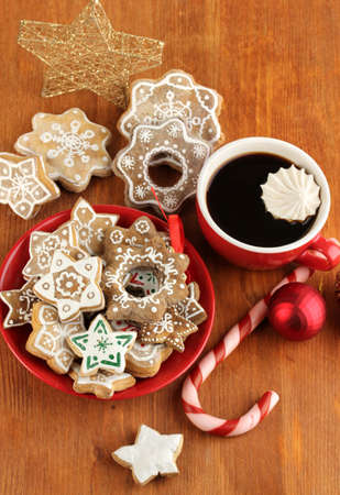 Christmas treats on plate and cup of coffe on wooden table close-up photo