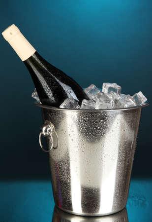 Bottle of wine in ice bucket on darck blue background photo
