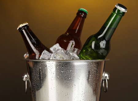 Beer bottles in ice bucket on darck yellow background photo