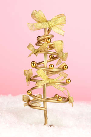Wire Christmas tree on pink background photo