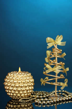 Wire Christmas tree with beads and candle on blue background photo